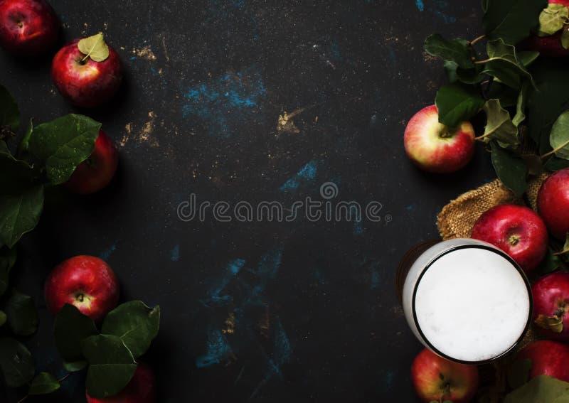 Sidra de maçã no vidro de cerveja com maçãs frescas, fundo preto, t foto de stock