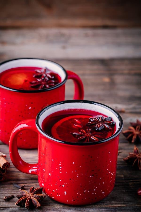 A sidra de maçã temperada da romã ferventou com especiarias a sangria do vinho em umas canecas vermelhas no fundo de madeira fotografia de stock royalty free