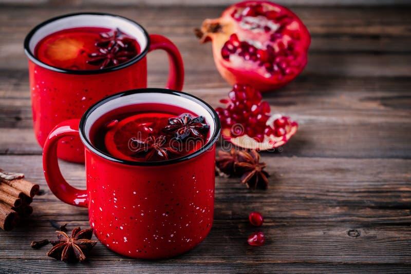 A sidra de maçã temperada da romã ferventou com especiarias a sangria do vinho em umas canecas vermelhas no fundo de madeira imagens de stock