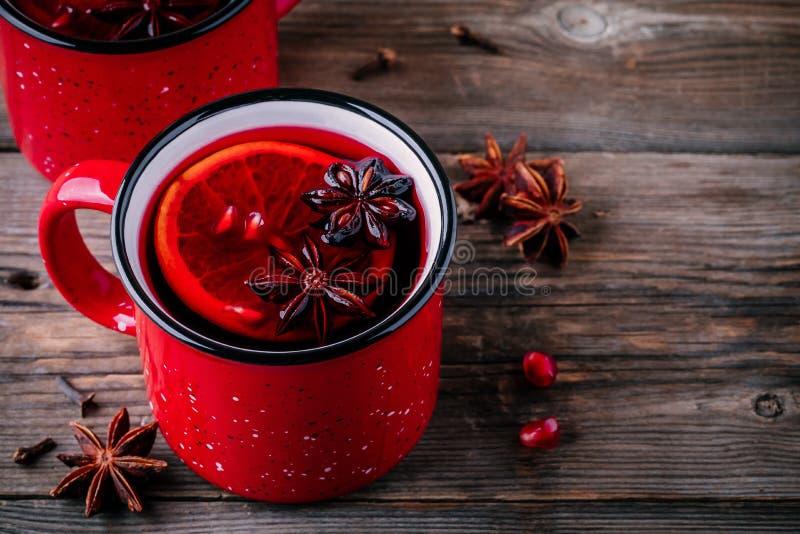 A sidra de maçã temperada da romã ferventou com especiarias a sangria do vinho em umas canecas vermelhas no fundo de madeira imagens de stock royalty free