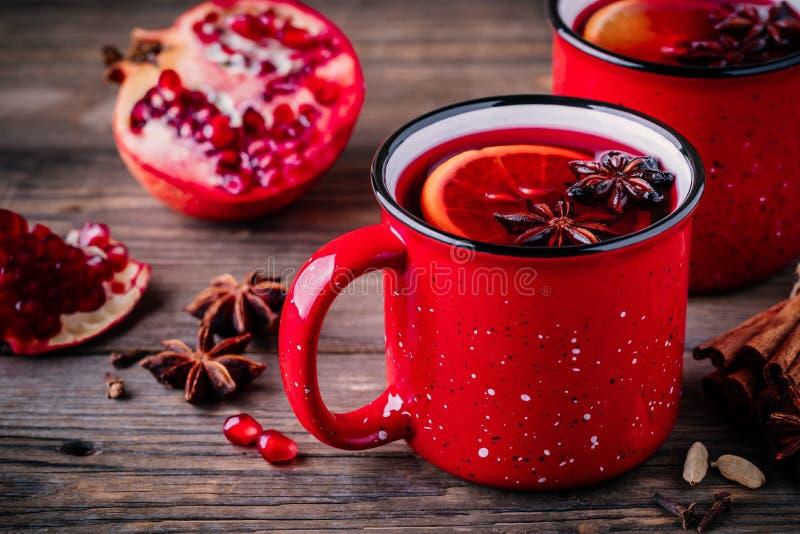 A sidra de maçã temperada da romã ferventou com especiarias a sangria do vinho em umas canecas vermelhas no fundo de madeira fotografia de stock