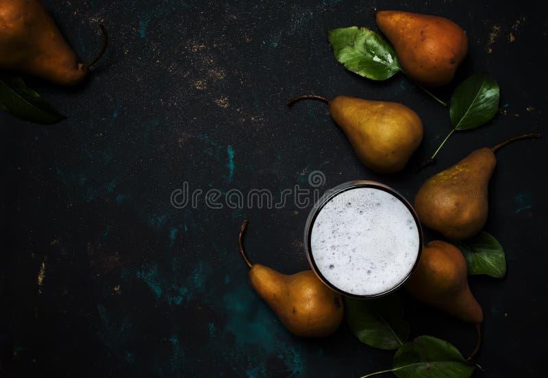 Sidra o cerveza hecha en casa de la pera con la espuma, fondo oscuro, visión superior imagen de archivo