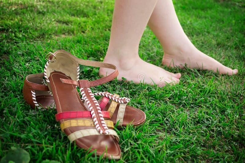 Sie entfernte ihre Sandalen und Wege barfuß auf dem Gras stockfoto