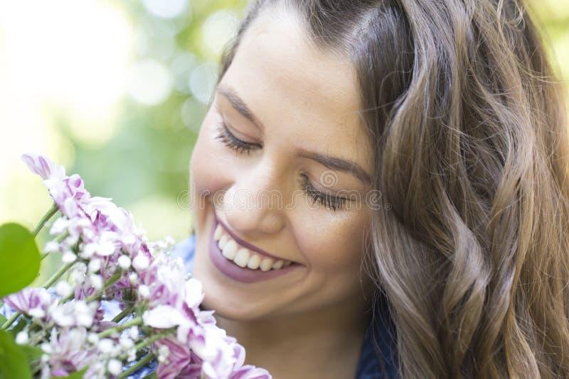 Sie genießt wirklich Blumen lizenzfreies stockbild