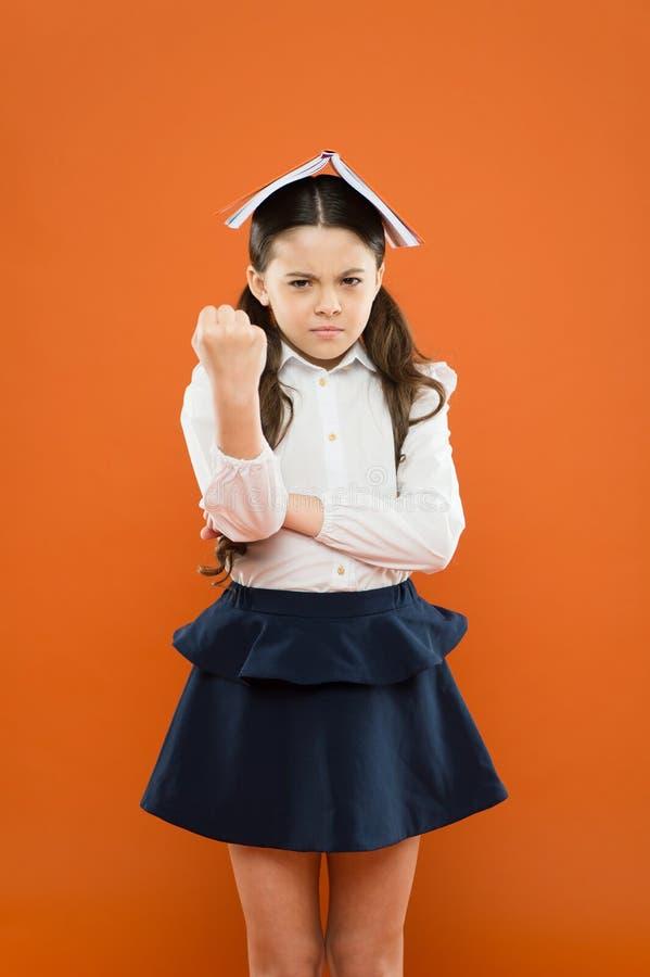 Sie hasst lesen Verärgertes kleines Kind müde vom Lesebuch auf orange Hintergrund Unglückliches kleines Schulmädchen, das hat stockfotografie