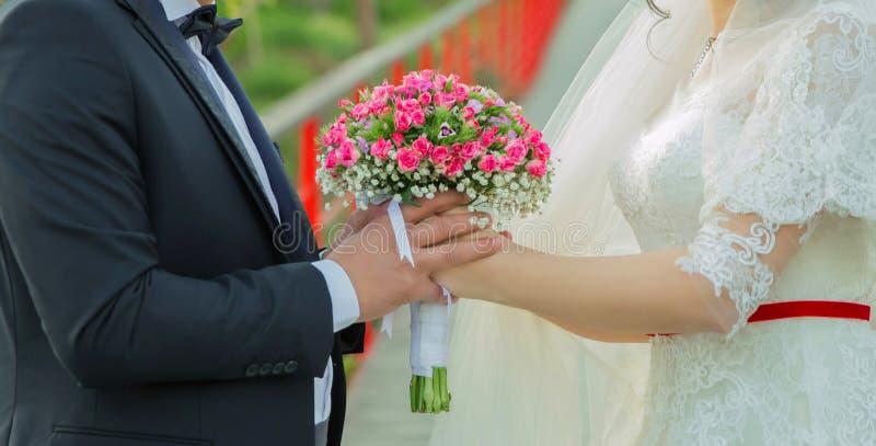 Sie hielten den rosa Blumenblumenstrauß in ihren Händen Hände falteten sich hinter ihrer Rückseite, halten einen schönen kleinen  stockfoto