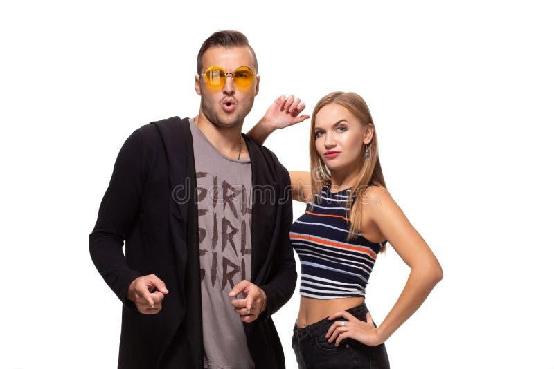 He Sie Junger erwachsener Mann in den gelben Gläsern und nette Blondine, die Finger zeigt und Kamera betrachtet lizenzfreie stockfotografie