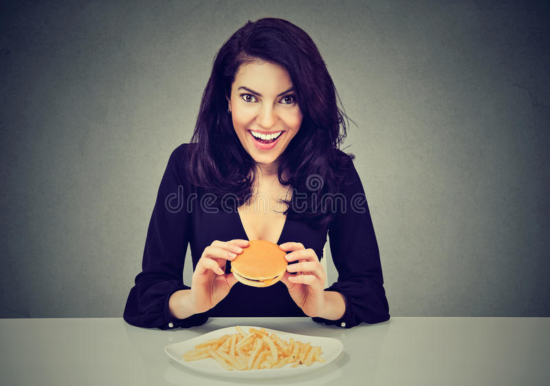 Sie mag Schnellimbiß Glückliche junge Frau, die Cheeseburger und Pommes-Frites isst lizenzfreie stockfotos