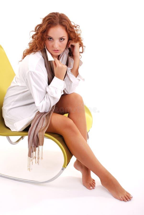 Sie sitzt auf Lehnsessel stockfoto