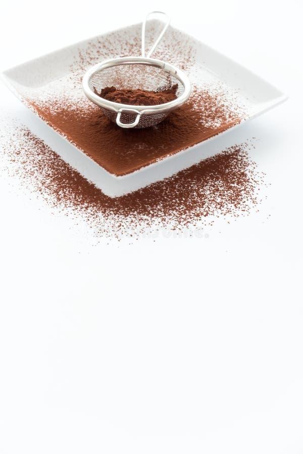 Sieb füllte mit Kakaopulver auf Porzellan-Platte und Weiß Rückseite stockbild