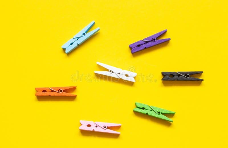 Sieben farbige Wäscheklammern auf einem gelben Hintergrund stockfotografie
