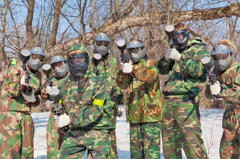Freunde in den Masken und in Tarnungsspiel Paintball stockfotos