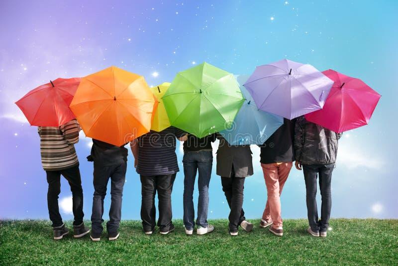 Sieben Freunde mit Regenbogenfarbenregenschirmen lizenzfreies stockfoto