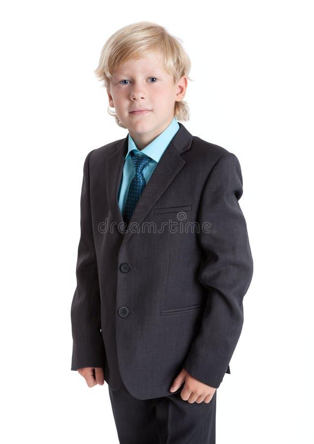 Sieben Jahre alte blonde Schüler in der Schuluniform, Anzug, Hemd und Bindung, lokalisierten weißen Hintergrund lizenzfreie stockbilder