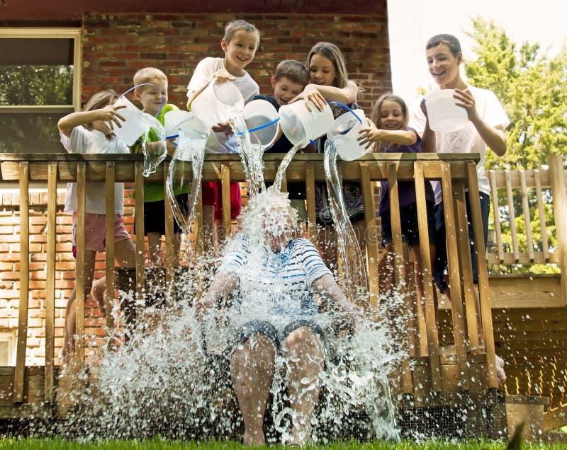 Sieben Kinder mit 7 Eimern entleeren Wasser auf Frau lizenzfreie stockbilder