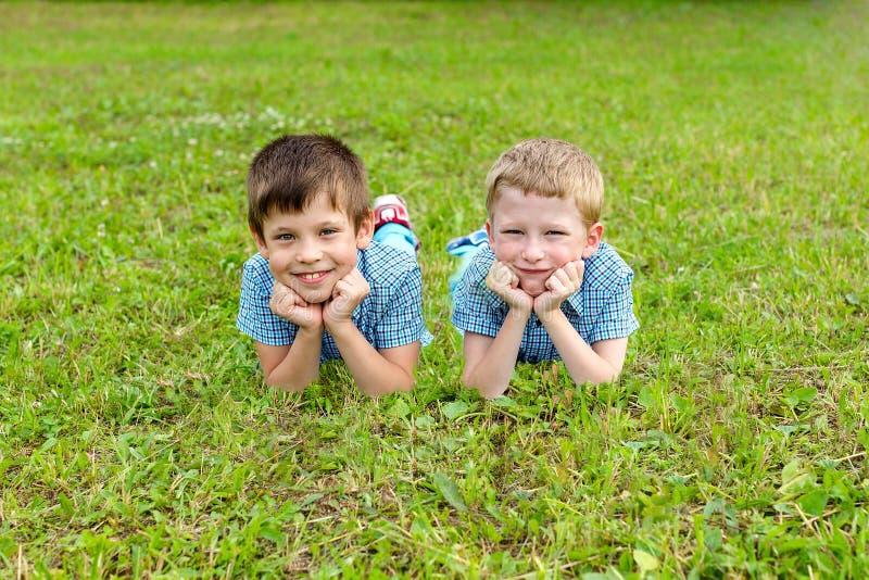 Siebenjährige Zwillinge liegen auf dem Rasen lizenzfreies stockfoto