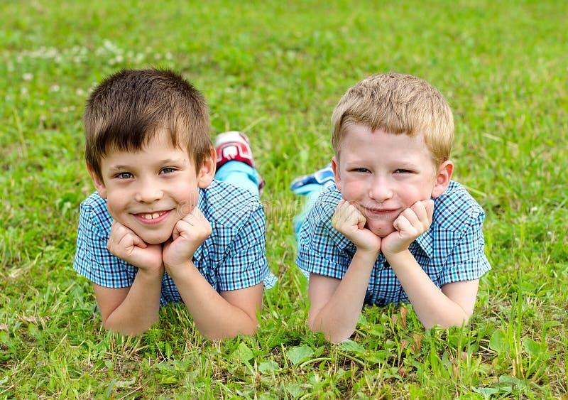 Siebenjährige Zwillinge liegen auf dem Rasen stockbilder