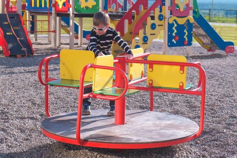 Siebenjähriger Junge, der auf das Karussell auf dem Spielplatz spinnt stockbilder