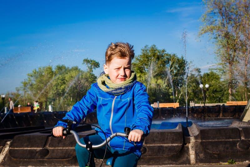 Siebenjähriger Junge, der ein Fahrrad im Stadt Park reitet Baby runzelt von der Sonne die Stirn stockbilder
