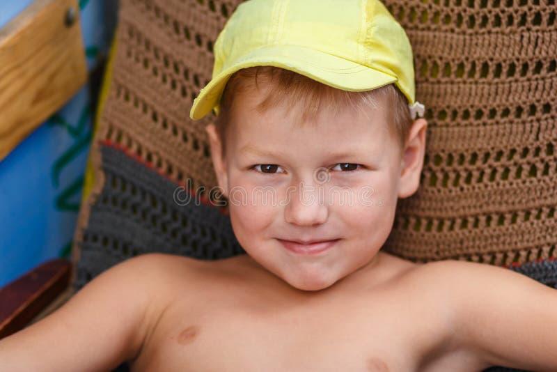 Siebenjähriger Junge in der gelben Kappe lizenzfreie stockbilder