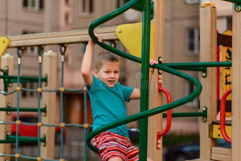 Siebenjähriger Junge in einem Türkist-shirt, das auf dem Spielplatz nahe dem Haus spielt lizenzfreies stockbild