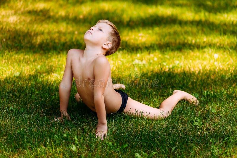 Siebenjähriges flexibles Kind in den Schwimmenstämmen führt akrobatische Übungen im Sommer auf dem grünen Gras durch lizenzfreie stockfotos