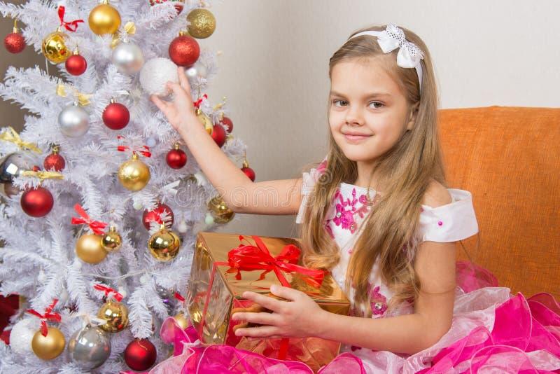 Siebenjähriges Mädchen im schönen Kleid sitzt mit einem Geschenk und dem Halten eines Weihnachtsballs in den Händen stockbild