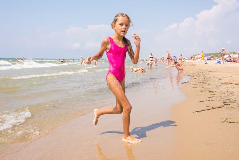Siebenjähriges Mädchen läuft auf Strand vom Meer stockfotografie