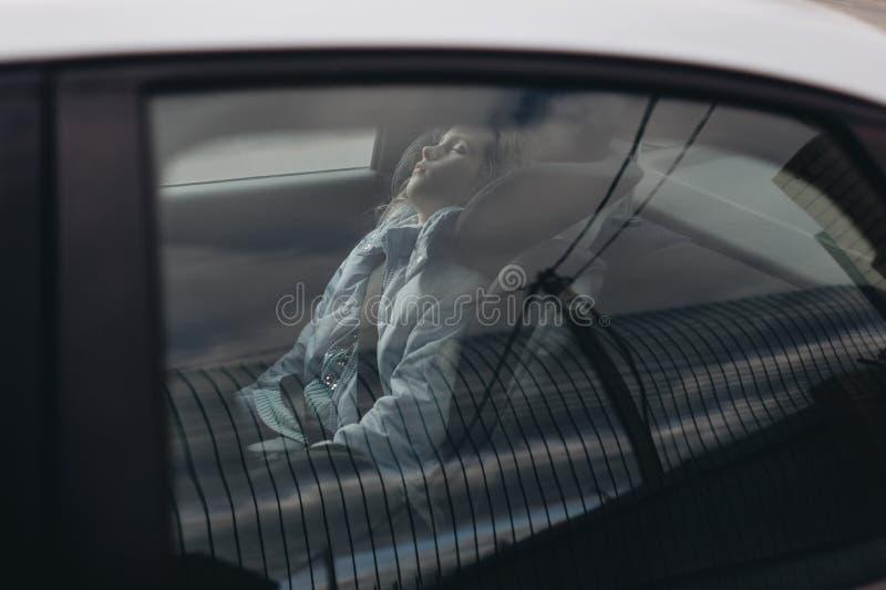 Siebenjähriges reizend Mädchen, das in einem Autositz der Kinder schläft stockfotografie