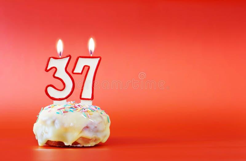 Siebenunddreißig Jahre Geburtstag Kleiner Kuchen mit wei?er brennender Kerze in Form von Nr. 37 lizenzfreies stockfoto