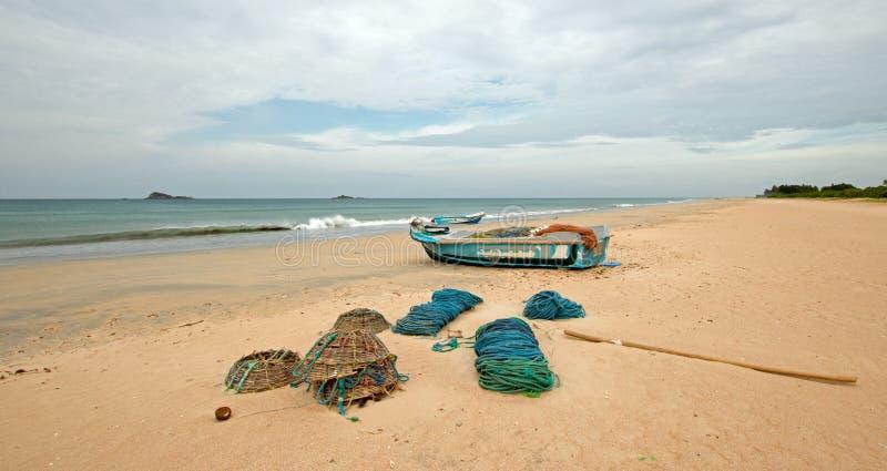Sieci, oklepowie, kosze i arkany obok łodzi rybackiej na Nilaveli, wyrzucać na brzeg w Trincomalee Sri Lanka fotografia stock