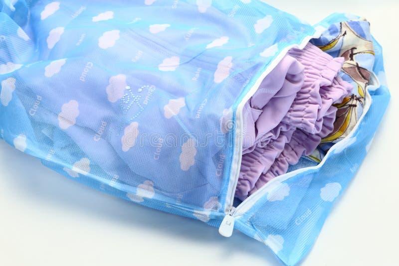Sieci pralniana torba dato che myć, odziewamy w pralce na białym tle zdjęcia stock
