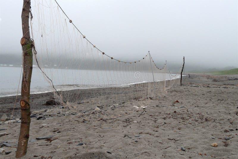 Sieci rybackie suszą na plaży w mgłowej pogodzie zdjęcia stock