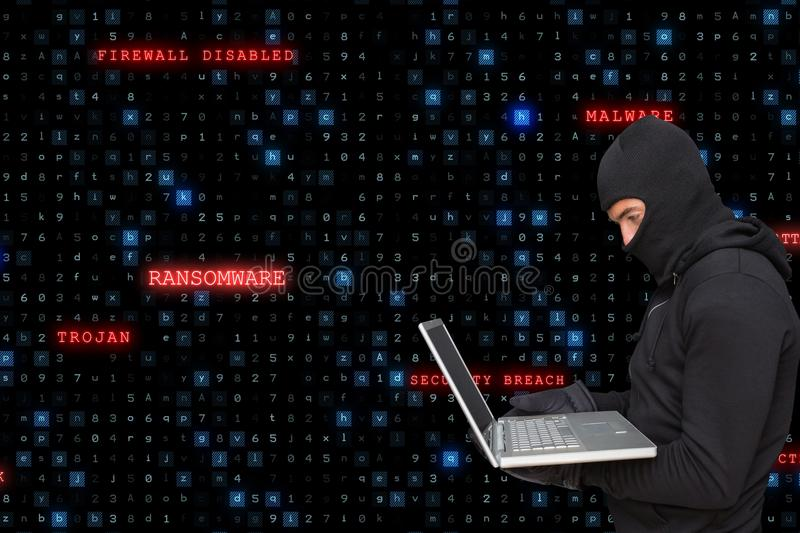 Sied view of cyber criminal wearing an hood is hacking from a laptop against matrix code rain backgr. Digital composite of hacker stock photography