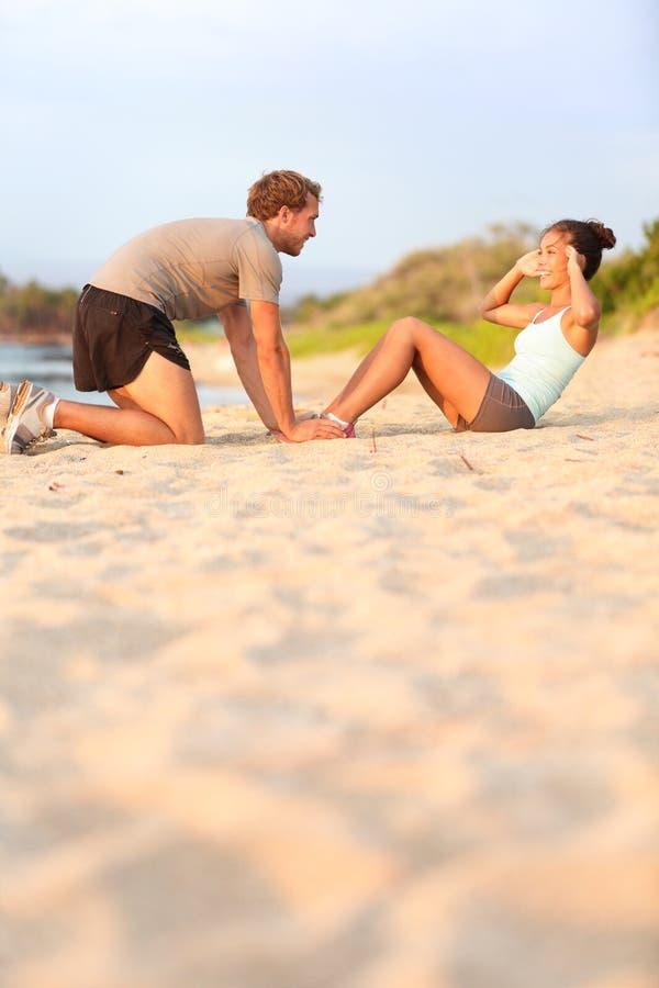 Sieda aumenta la donna di forma fisica - maschio che aiuta sorridere felice fotografia stock