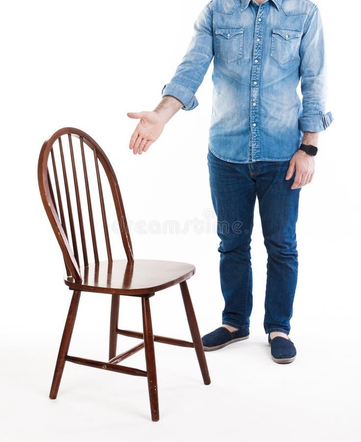 Sieda giù per favore Un uomo nell'usura di stile casuale mostra la sedia rustica di legno Uomo e sedia isolati su fondo bianco fotografia stock