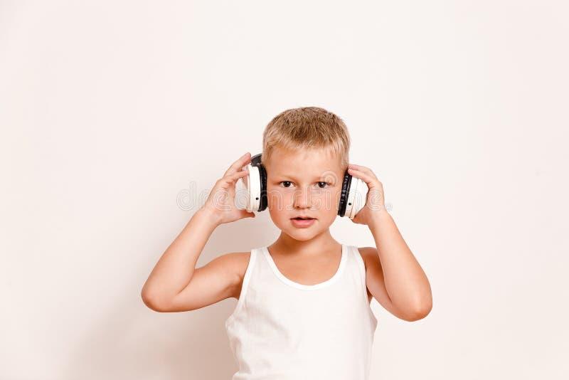 Siedmioletni dziecko słucha muzyka przez wielkich pełnych rozmiarów hełmofonów na białym tle zdjęcia stock