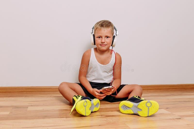 Siedmioletni garbnikujący dziecko siedzi na podłodze z smartphone w jego ręki w jasnozielonych sneakers i hełmofony na jego przew obraz royalty free