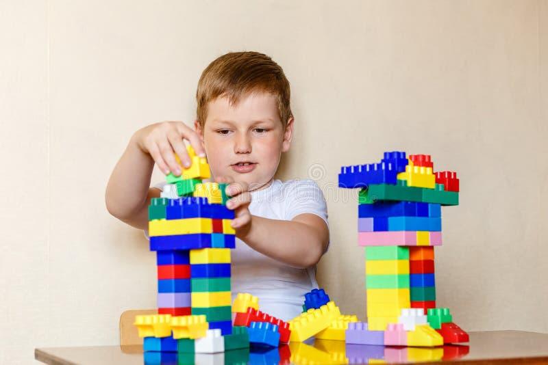 Siedmioletnia chłopiec buduje postacie od wielkich plastikowych części obraz royalty free