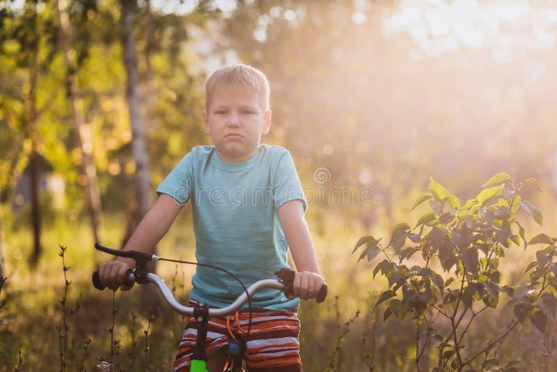 Siedmioletnia chłopiec jedzie bicykl w miasto parku z powrotem w lato zmierzchu świetle zdjęcie royalty free