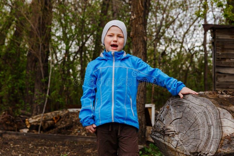 Siedmioletnia chłopiec w windbreake błękitnych krzykach radość w wiośnie zdjęcia royalty free