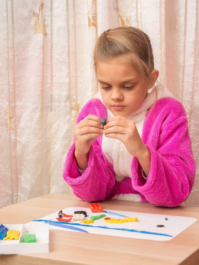 Siedmioletnia dziewczyna z entuzjazmem sculpts fotografia royalty free