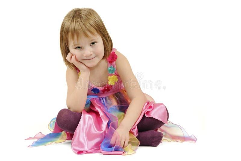 Siedząca dziewczyna w kolorowej sukni zdjęcie royalty free