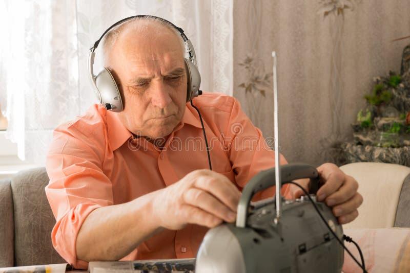 Siedzącego starego człowieka Słuchająca wiadomość przy radiem fotografia stock