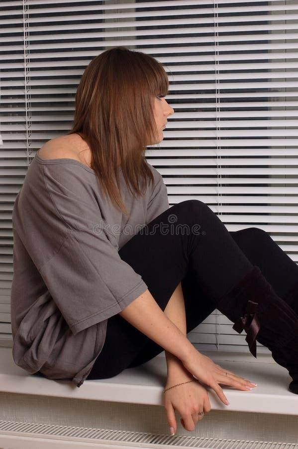 siedzący brunetki okno obrazy royalty free