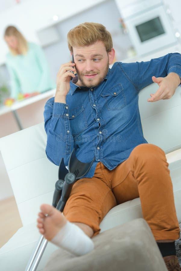 Siedzący młody człowiek z kostki zwichnięciem fotografia stock