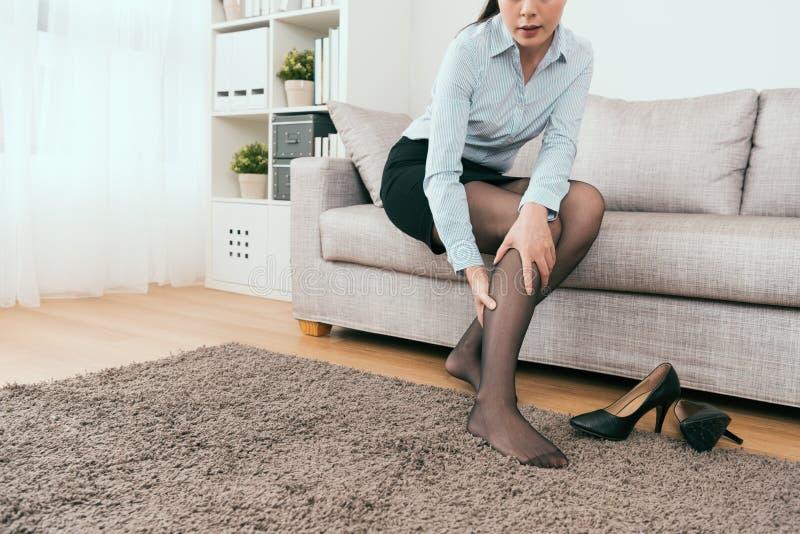 Siedzący na kanapy odczuciu nogi drętwienie obrazy royalty free