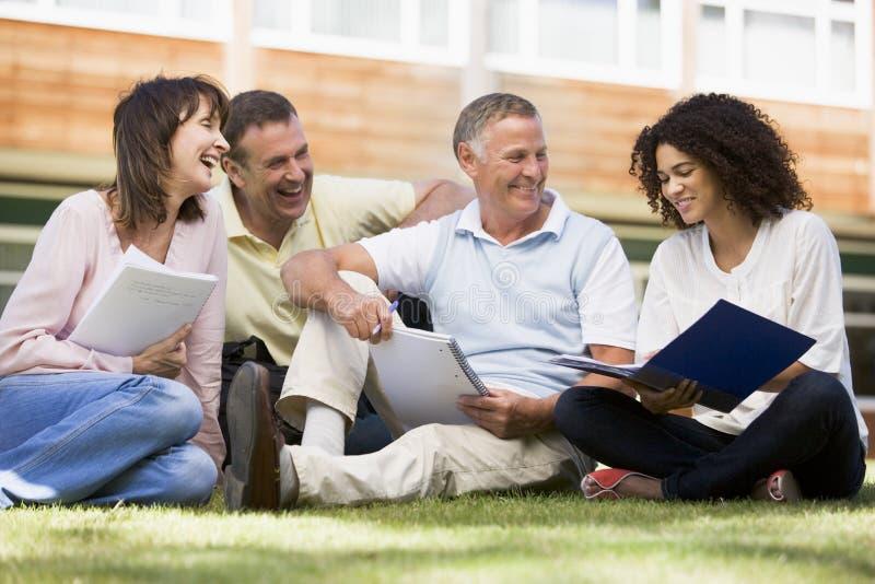 siedział dorosłych studentów uniwersytetu trawnika obrazy stock