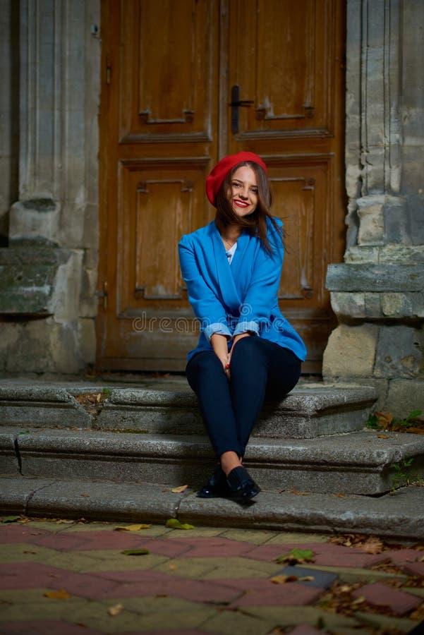 Siedzieć na ganeczku w czerwonym berecie obraz stock