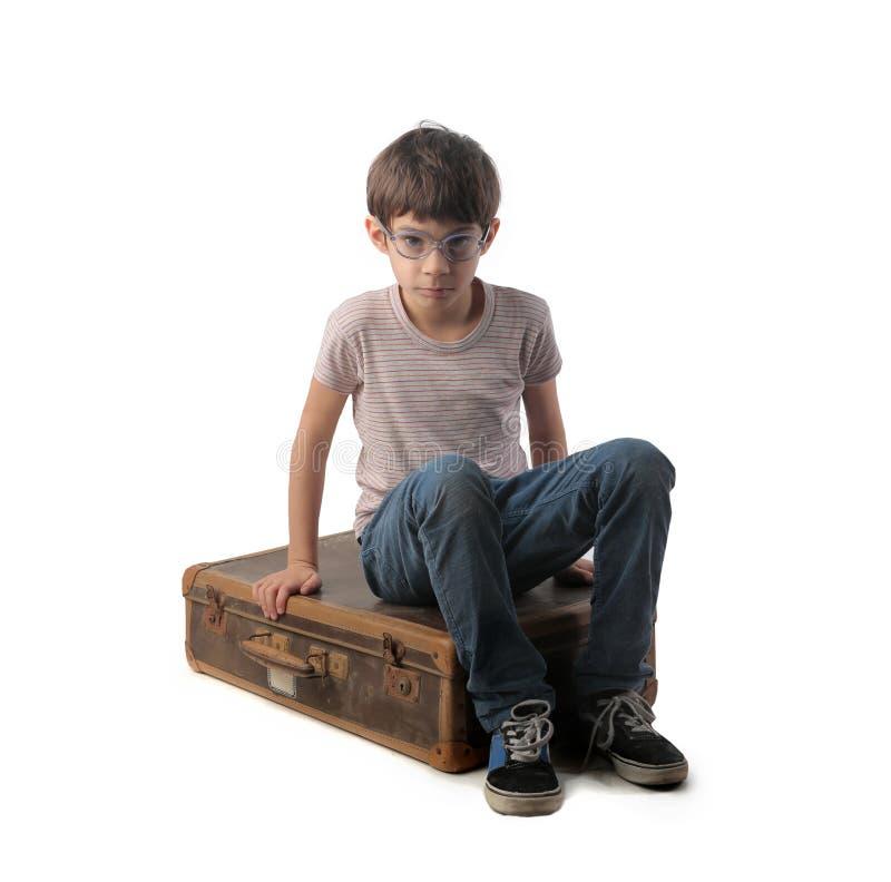 Siedzieć na starej walizce zdjęcia stock